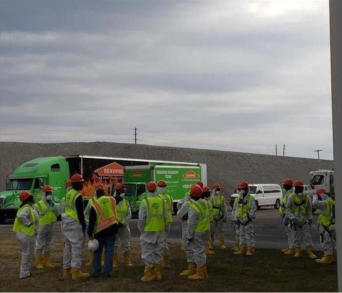 Twenty-plus SERVPRO workers staging outside of large SERVPRO semis and trucks during storm event