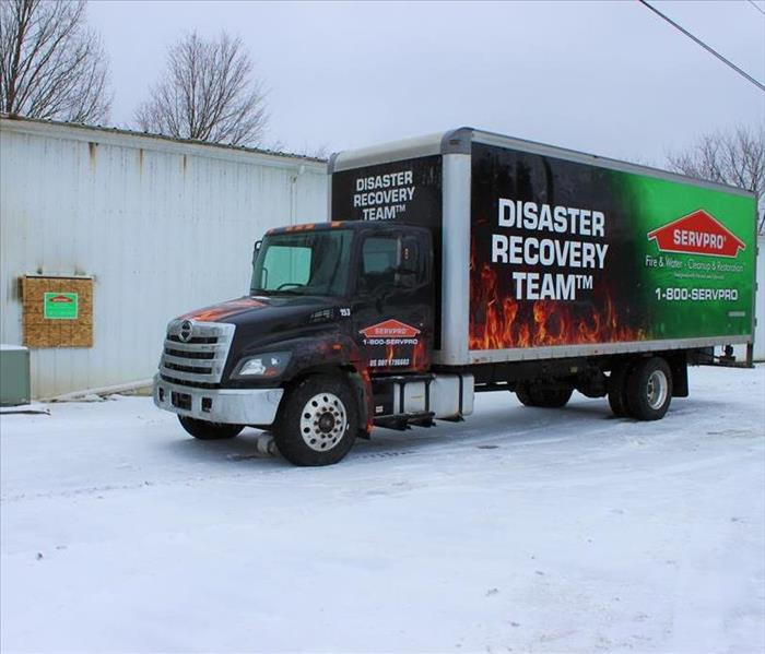 SERVPRO box truck outside building that has fire damage