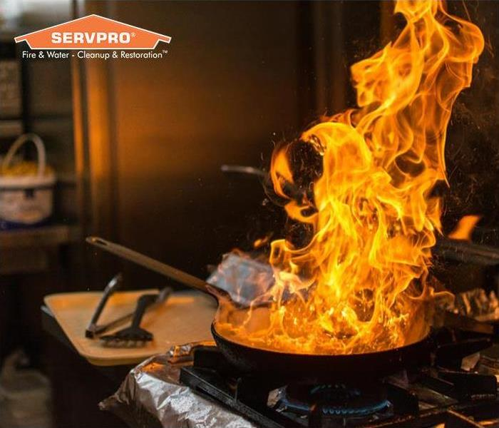 Close up of grease fire over stove with SERVPRO logo