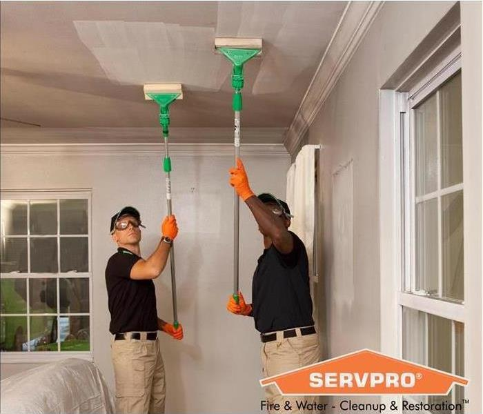 Two male SERVPRO employees cleaning ceilings after fire