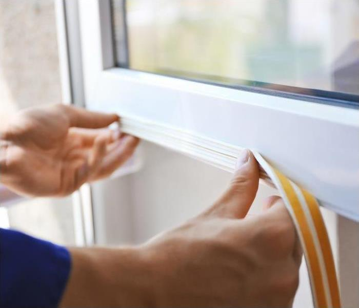 a person placing weatherstripping on a white window