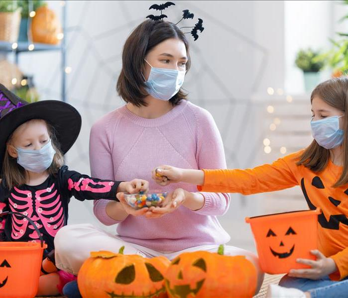 Family putting candy in buckets with masks on