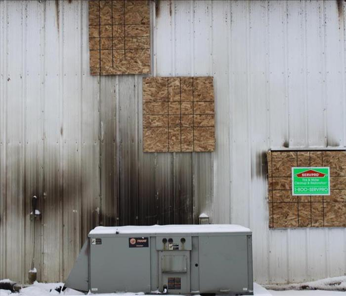 Structure boarded up after fire with SERVPRO logos